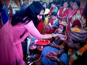 Meena putting Tikka on the groom's forehead.